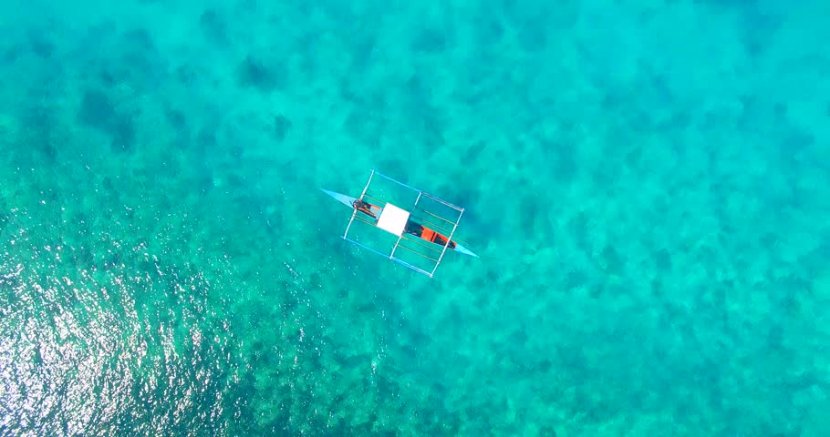 Bird's eye aerial shot of a filipino boat floating on top of beautiful blue waters on Siargao Island, Philippines