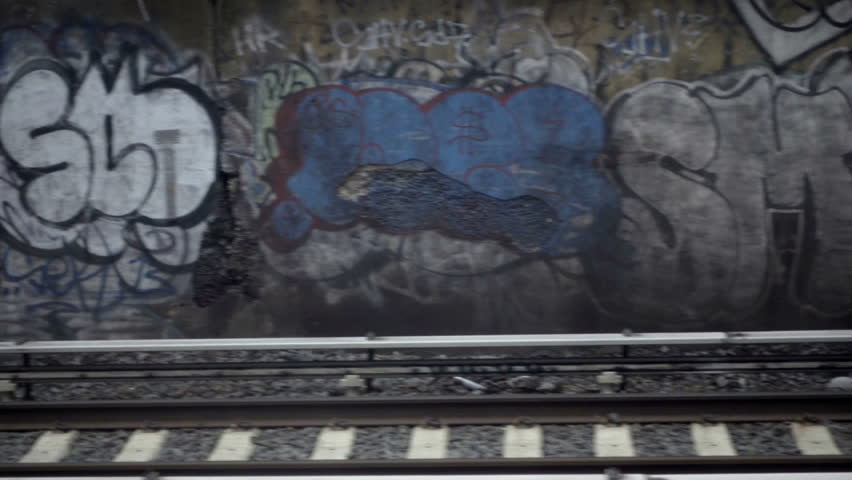 Graffiti on wall passing from moving subway train view above gritty tracks in NYC slow motion
