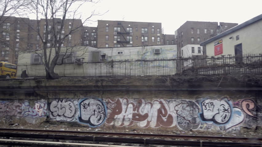 Moving subway view of graffiti on urban walls in poverty stricken neighborhood in Brooklyn NYC