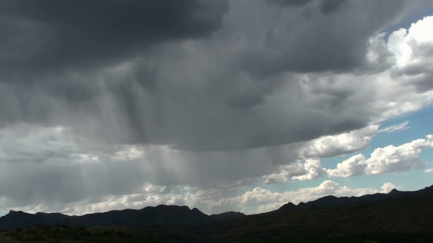 Time Lapse, Rain shafts sweep across silhouetted mountains dumping precipitation, followed by clearing blue skies. 1920x1080