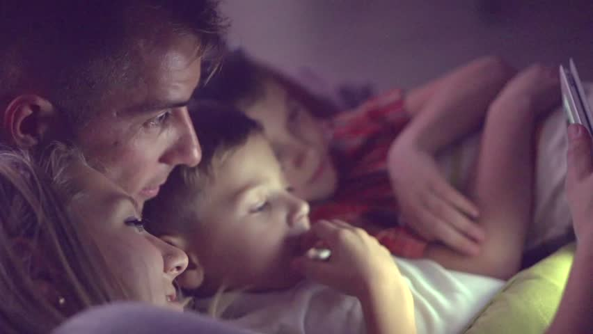 Happy family- Father, mother and Two kids lying down on the sofa and using tablet pc at night. Family watching movie on tablet computer in a dark room. HD 1080p, slow motion 240 fps, high speed camera #14842069