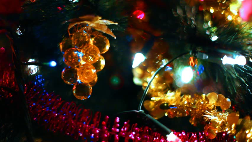 toy in form of glass grapes hanging on Christmas tree among glowing garlands, close-up