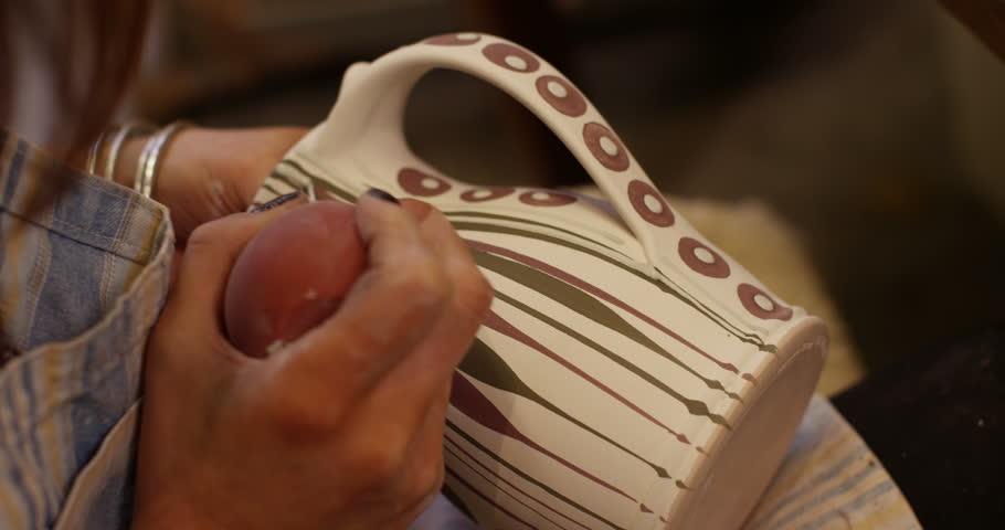 Close-up shot of a young woman at workbench painting ceramics in pottery studio. Royalty-Free Stock Footage #14845297