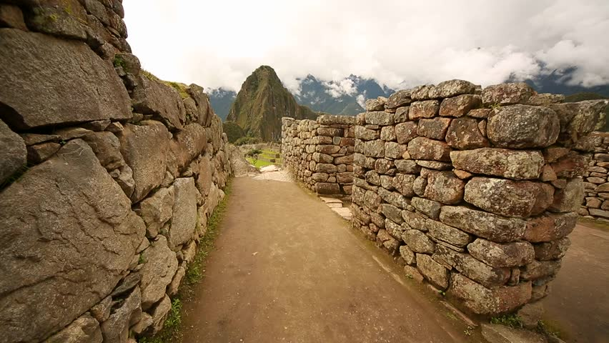 Walking in the buildings of Machu Picchu to the classical view of Machu Picchu with Wayna Picchu. Ideal for a time lapse video.