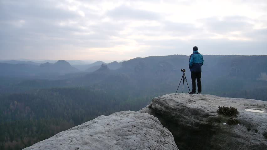 Photographer in blue jacket at tripod  on rocky view point and taking photos of misty morning landscape. Hike in rocks. Melancholic autumn morning.  | Shutterstock HD Video #14871793