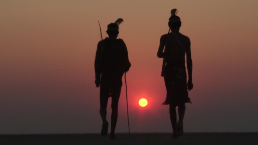 Bushmen walking into the sunset on the Makgadikgadi Pans - Botswana