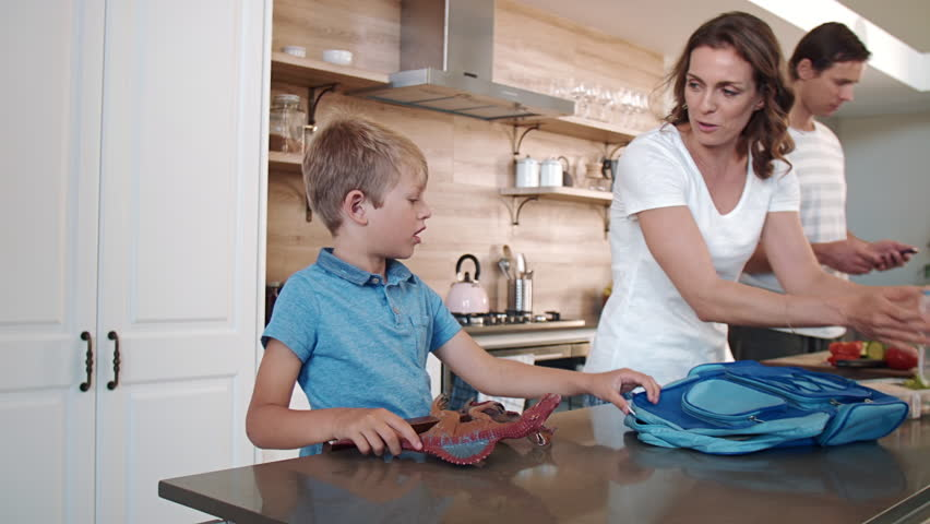 Mother helping her child son pack his school bag before dad takes him to school #14910847