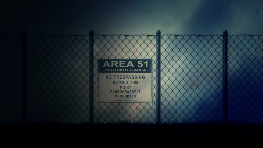 Zoom in into an Area 51 Sign on a Metal Fence on a Stormy Night