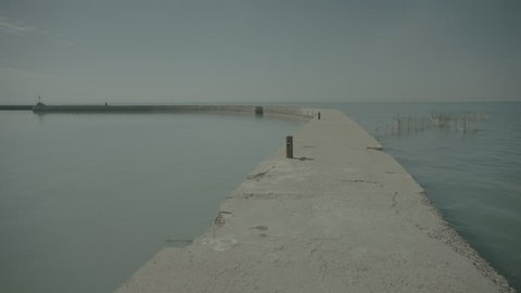 The Gulf Sea. Wide shot of a curving jetty and a smooth as oil sea. Cage fish nets standing tall in the sea can be seen on the right of frame.
