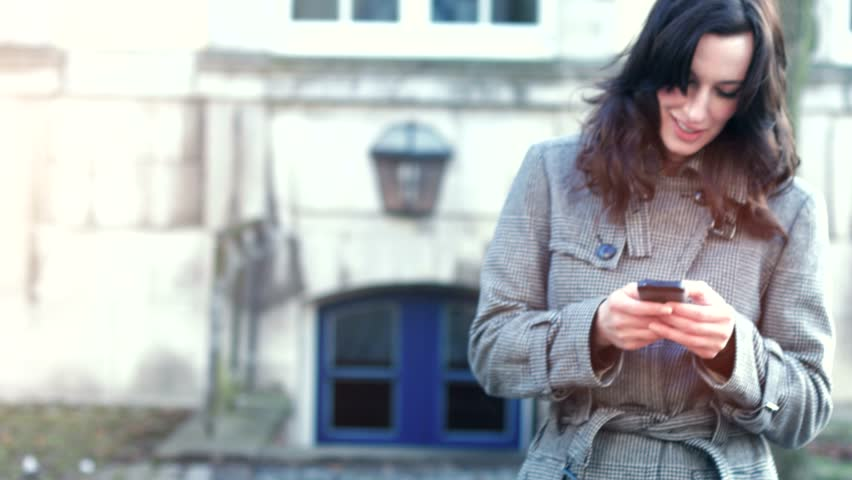 Businesswoman use her mobile phone outdoor in a historic village | Shutterstock HD Video #14934004