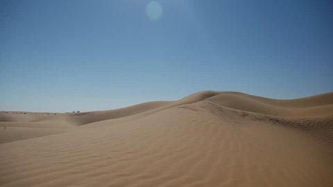 SAHARA DESERT,  TUNISIA - CIRCA OCTOBER 2015:  photographer walks barefoot  on a dune in the desert.