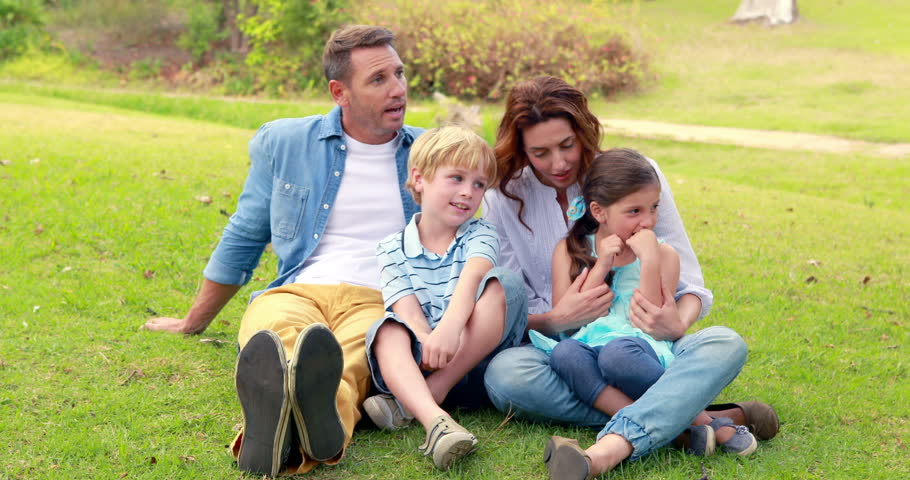 Happy family sitting on grass in park | Shutterstock HD Video #14955562