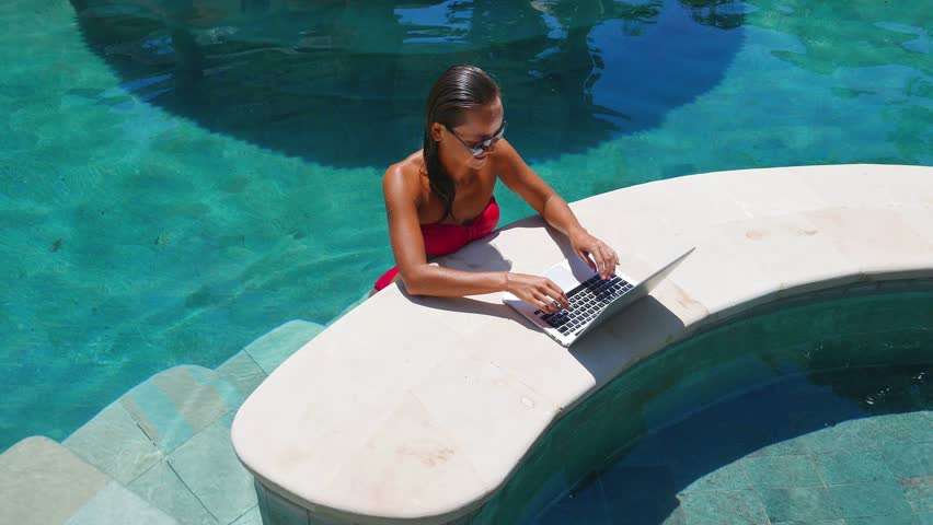 Woman working on her laptop computer sitting at poolside. Beautiful young female model working freelance at swimming pool on laptop. Villa. Royalty-Free Stock Footage #14963308