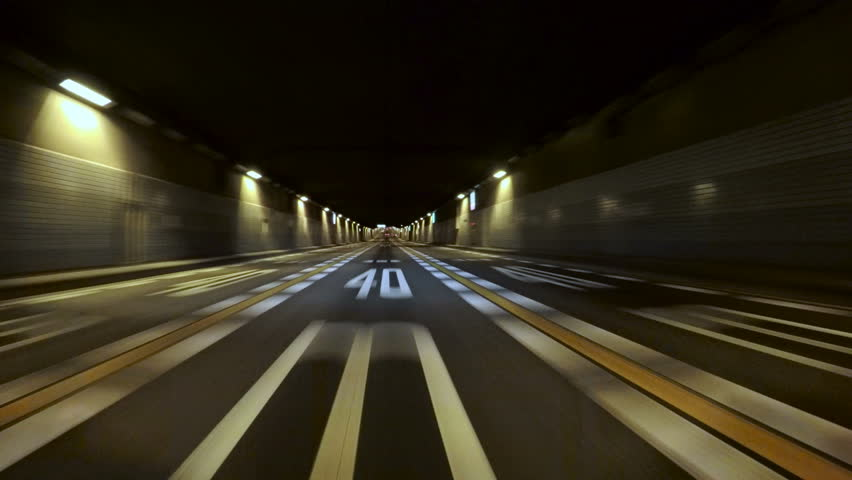 Driver POV entry to the Tokyo Bay Underpath on the Bayshore Freeway. Yellow and white lane stripes and random illumination through the tunnel. | Shutterstock HD Video #14964916