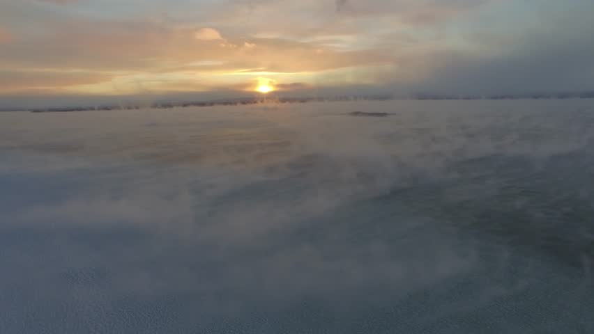 An drone aerial 4K flight above a frozen lake - Lake Champlain in Vermont, with clouds moving slowly across the lake surface at sunrise UHD