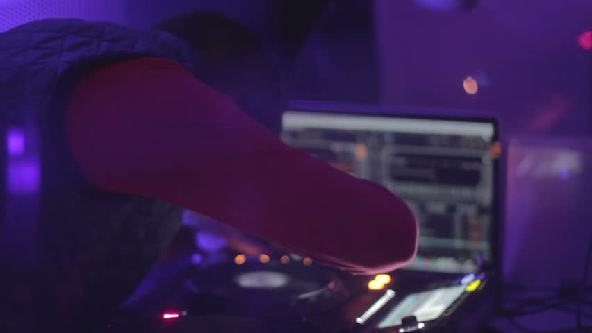 Skilled dj working hard at the mixing console, playing music. People having fun   Shutterstock HD Video #14999893