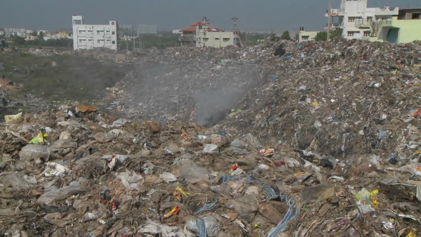 Smoke rises from burning rubbish in a large urban land-fill.