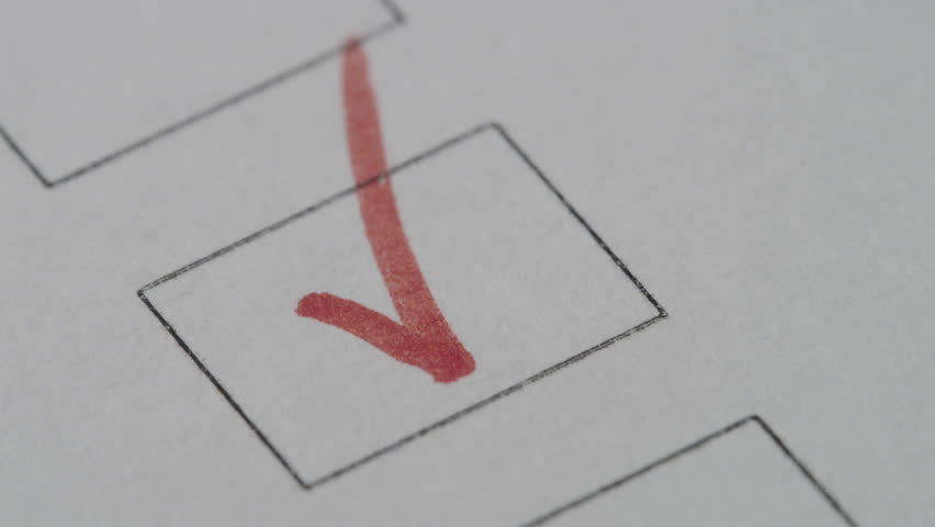 Marker puts a tick in the box on white paper close-up