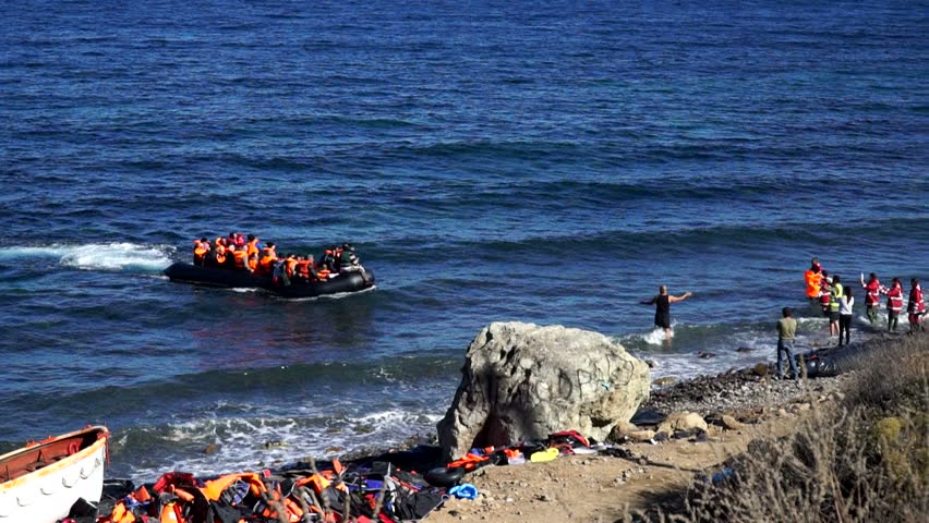 Refugees swim up to the coast by the boat. Lesbos, Greece. October 14, 2015. A dangerous and illegal way through the sea from Turkey to the Europe. People help them to get out of the boat ashore. | Shutterstock HD Video #15010237