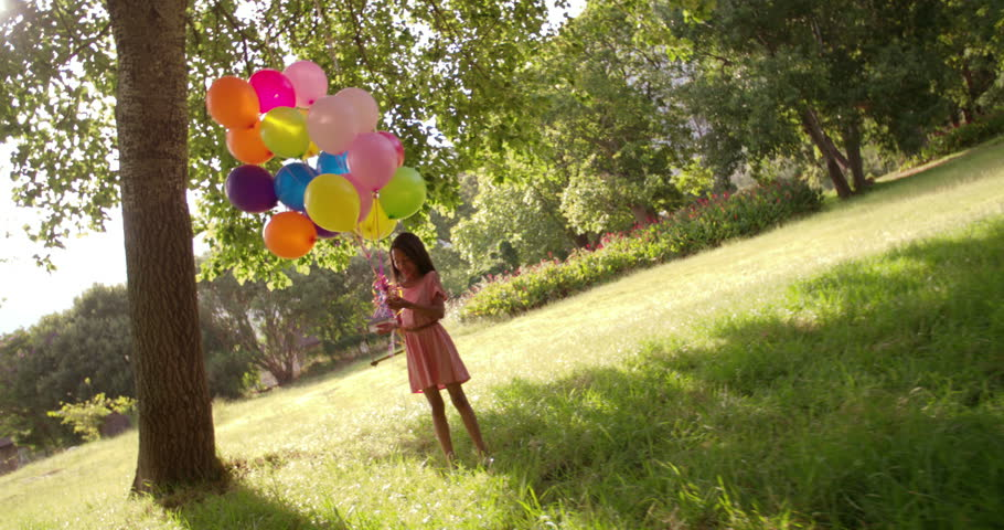 Sweet brunette long haired African-American girl in a pink dress running in a sunny green park with a big bundle of colourful helium balloons on strings. | Shutterstock HD Video #15046801