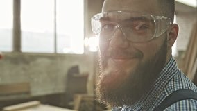 Closeup view of one handsome young adult man worker with a beard and goggles. RAW video record.