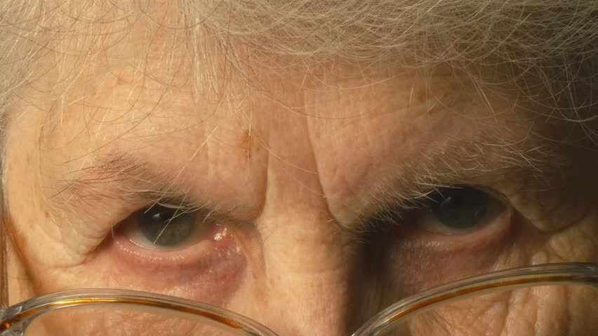 A very old woman puts on glasses and looking at the camera   Shutterstock HD Video #15053764
