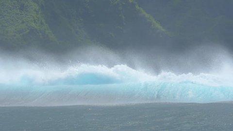 SLOW MOTION CLOSE UP: Big Teahupoo wave splashing towards exotic island Tahiti in sunny summer