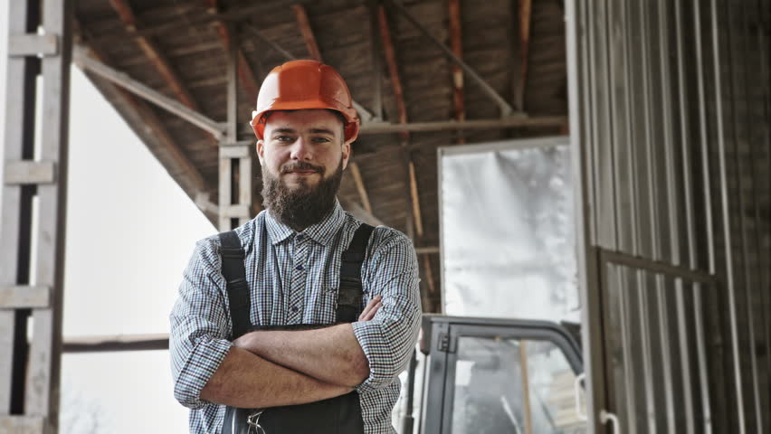 Portrait of cheerful bearded handsome young adult industrial engineer wear plastic helmet uniform against the background of loader. RAW video record. #15055162