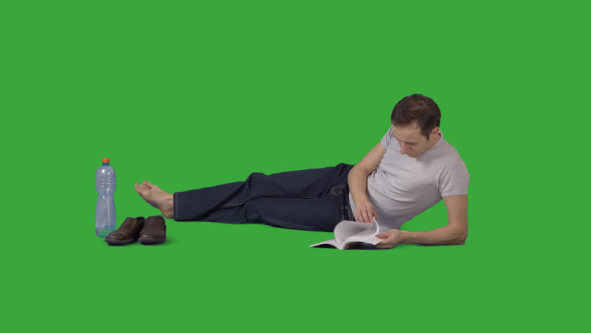 Attractive barefooted man is lying on side and reading book. Footage with alpha channel. File format - mov. Codec - PNG+Alpha Combine these footage with other people to make crowd effect