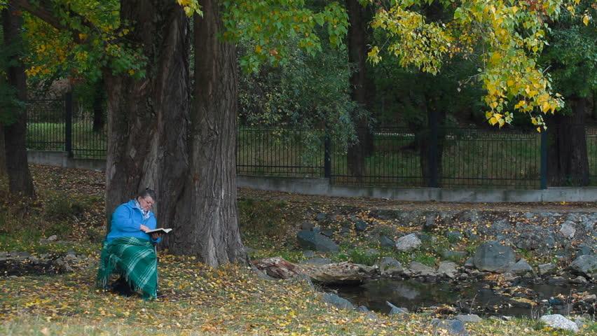 Senior woman enjoying his retirement in chair under autumn tree, reading book. | Shutterstock HD Video #1506338