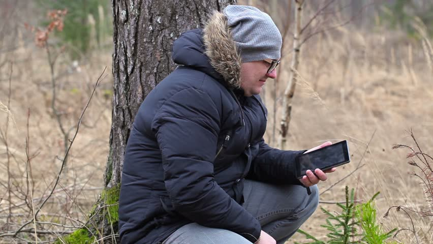 Sad man with the smart phone in the forest | Shutterstock HD Video #15073465