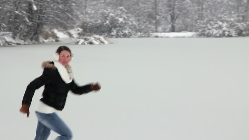 Happy girl playing in the snow by the lake | Shutterstock HD Video #15111307