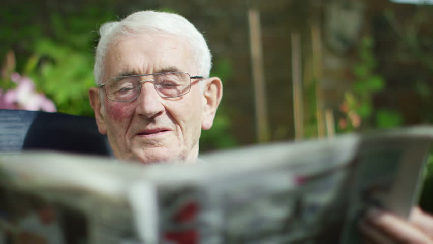 4K Portrait of elderly man sitting alone reading newspaper in the garden | Shutterstock HD Video #15124831