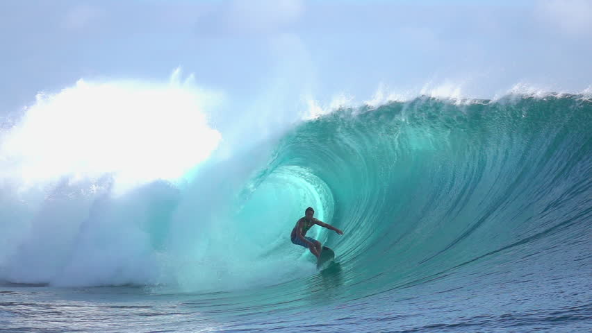 SLOW MOTION: Cheerful extreme pro surfer surfing inside big tube barrel wave Teahupoo in crystal clear Pacific ocean in sunny Tahiti island