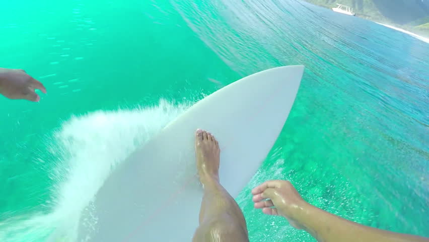 FPV SLOW MOTION: Extreme pro surfer paddling and standing up on surfboard, riding big tube barrel wave Teahupoo in crystal clear Pacific ocean in sunny Tahiti island
