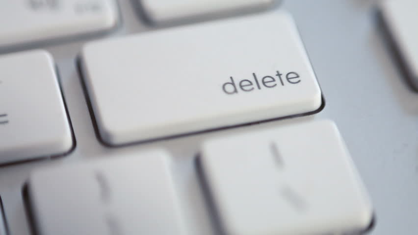 An extreme close up of a finger pressing the DELETE key once, then furiously. #1516234