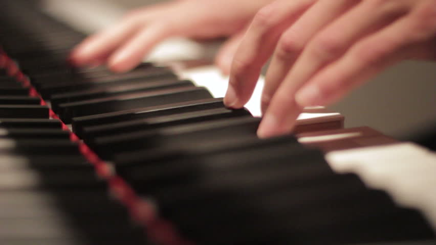 Two hands playing a gentle piece on a beautiful grand piano. A recording of the reflection using a shallow depth of field.
