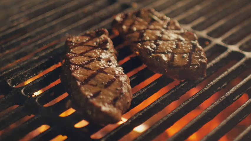 Cooking delicious juicy meat steaks on the grill on fire