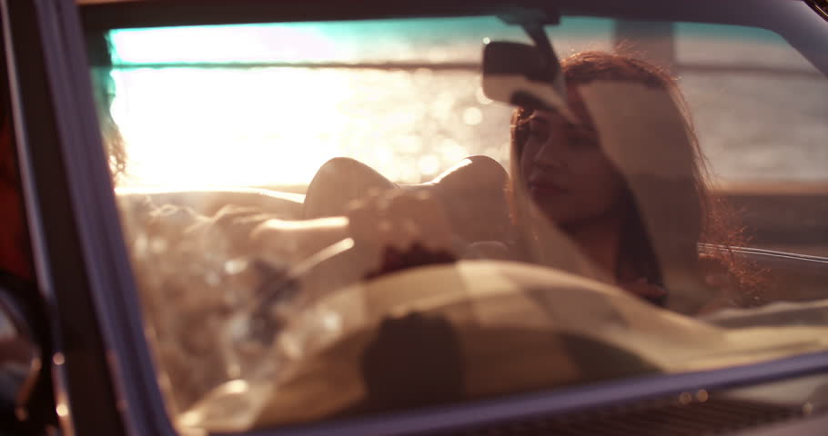 Hipster boy posing while his girlfriend taking pictures with a smartphone sitting in a convertible parked close to the beach with sunset sun flare | Shutterstock HD Video #15173242