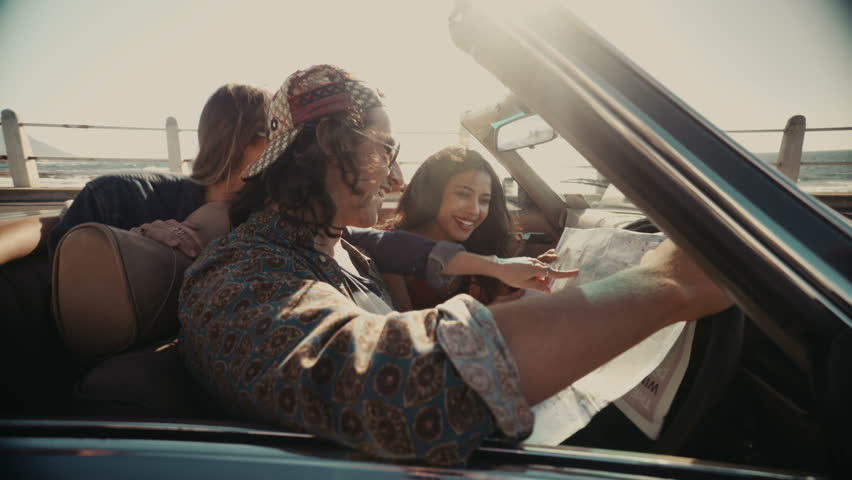 Group of multi-ethnical hipster friends looking at a road map from the inside of a convertible, planning their next adventure   Shutterstock HD Video #15174169