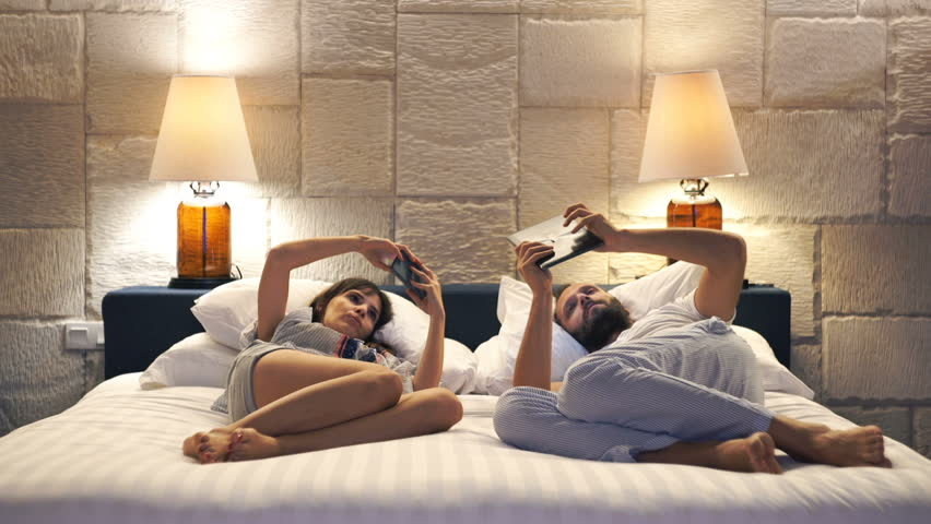 Young couple with smartphone and tablet lying on bed late at night at home  | Shutterstock HD Video #15195232