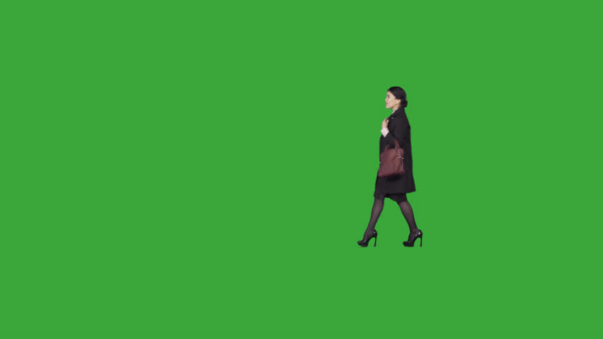 Beautiful, fashionable asian young woman in dark raincoat & with shopper bag slowly strolls, looks around. On alpha matte. File format - .mov, codec PNG+Alpha. Shutter angle -180 (native motion blur)