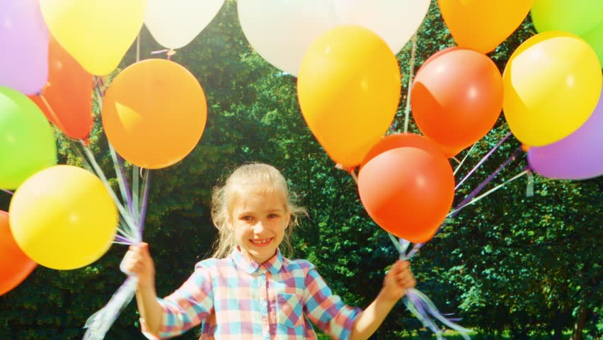 Closeup portrait laughing girl wich has a lot of balloons. Child whirling in the park | Shutterstock HD Video #15220144