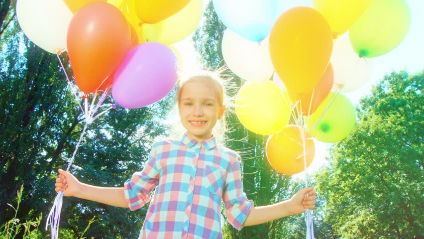 Closeup portrait girl walking at camera with balloons in the park and spinning at camera | Shutterstock HD Video #15220255