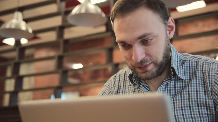Man working on modern laptop in cafe | Shutterstock HD Video #15225565