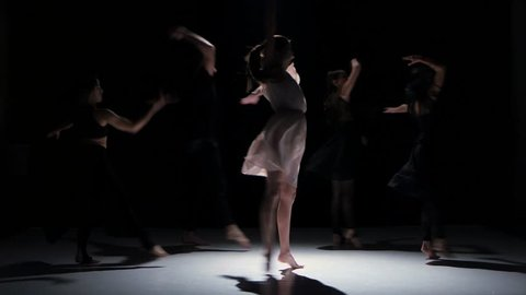 Contemporary dance moves of five dancers on black, shadow