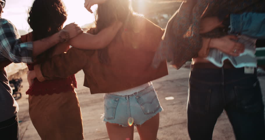 Back view of a group of teen hipster friends enjoying a walk on the pier hugging each other with sunset sun flare