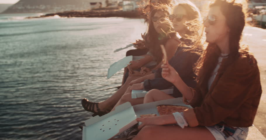 Group of hipster friends eating pizza sitting on the dock at the harbor during a summertime road trip