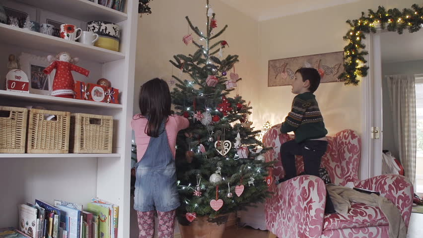 Mum Helps Son Decorate The Top Of A Christmas Tree