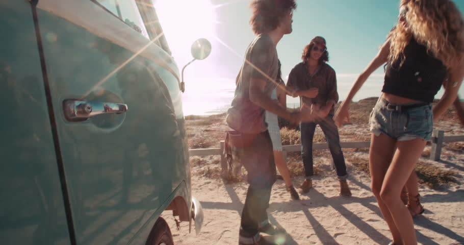 A group of multi-ethnic hipster road trip friends laughing and talking while dancing next to a parked retro van next to a sandy beach during sunset